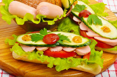 Big appetizing fast food baguette sandwich with lettuce, tomato Royalty Free Stock Images