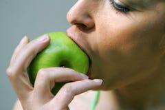 Big apple bite. Girl taking a bite on a apple stock image