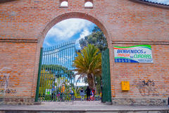 Big arch of brick entrance to a great park, parque las cuadras in Quito. Inside a palm tree and people on bycicle Royalty Free Stock Images