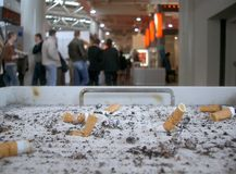 Big Ashtray at Fairground. Big ashtray in the foreground, filled with many cigarettes, surrounding computer exhibition (fair) in the background Stock Images