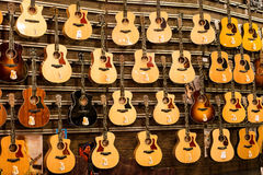 Big assortment guitars at the Siam Paragon Mall in Bangkok, Thailand. Stock Photos