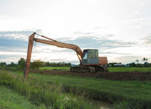 The big backhoe excavator machine in the green rice field Royalty Free Stock Photos