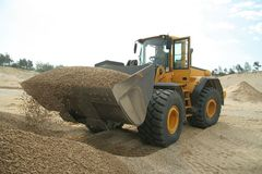 Big backhoe and full bucket. On working area Royalty Free Stock Photos