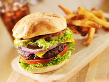 Big bacon cheeseburger. Bacon cheeseburger with lettuce and tomato royalty free stock photography