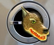 Big bad wolf head in washing machine nasty surprise attack. Conceptual photo of a big bad wolf head emerging from a washing machine door depicting nasty surprise royalty free stock photos