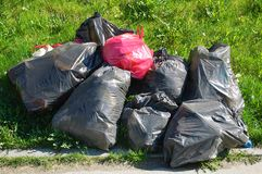 Big bags of garbage in the bright sun. They lay on green grass royalty free stock photo