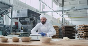 Big bakery industry funny baker with beard preparing the dough for baking bread and dancing at the same time while. Listening music from wireless headphones stock video footage
