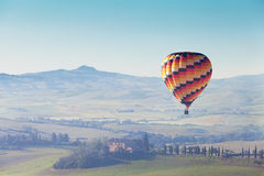 Big balloon flies over rural houses Stock Images