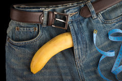 Big Banana like the penis, centimeter and men's jeans Royalty Free Stock Image