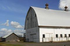 Big Barn, Little Barn. A little barn sits next to a big barn stock photo