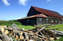 Big Barn with Rusted Tin Roof. A view of a big barn with a rusted tin roof in front of a pile of various cut logs, in Quebec, Canada Royalty Free Stock Photo