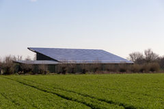 Big barn with solar panels and green field Stock Image