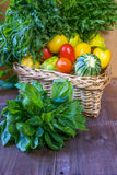 The big basket with basil, arugula and spinach on a wooden table Stock Photo
