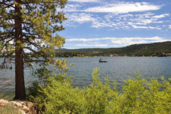 Big Bear Lake. A lone boat makes its way across Big Bear Lake in the Southern California mountains stock images
