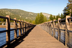 Big Bear Lake. A very low sun casts beautiful deep yellow light on a waterfront walkway along Big Bear Lake Royalty Free Stock Photos