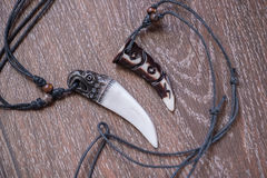 Big bear tooth and bone pendants carved from deer on a brown bac Royalty Free Stock Photography