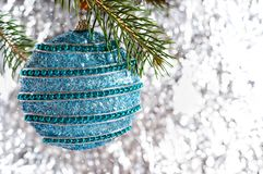 Big beautiful blue ball, green branch of spruce on a light blurred background. Festive greeting card. New Year, Christmas background. Free space for the stock photos