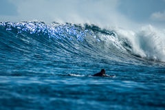 Big beautiful blue wave. Scenery of big beautiful blue wave and white foam in the ocean. Man on a surfboard at foreground Stock Photo