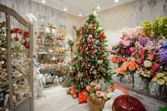 Big and beautiful decorated Christmas tree in a shop. Big and beautiful decorated Christmas tree in a flower shop with bouquets and cute souvenirs Royalty Free Stock Images