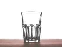 A big beautiful empty glass for water, juice or milk on a dark brown wooden table, isolated on a white background. A big empty transparent water drinking glass Royalty Free Stock Images