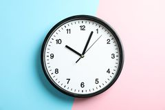Big beautiful office clock on two tone solid color stock photo