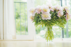 Big beautiful pale pink peonies bouquet in glass vase over window background. Light Home  decoration with flowers and vase. Royalty Free Stock Photos