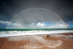 Big beautiful rainbow over ocean waves Stock Photos