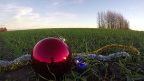 Big beautiful red Christmas bauble on December young wheat field, time lapse 4K. Big beautiful red Christmas bauble on December young wheat field, New year stock footage