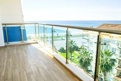 Beautiful new apartment building, outdoor, terrace view on seaside, sea ocean, palm trees. Exotic vacation city, California. Big beautiful terrace balcony of Stock Photography