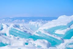 Big Beautiful turquoise blue ice on the Frozen Lake Baikal with mountains on the background. Big Beautiful blue ice on the Frozen Lake Baikal with mountains on Stock Images