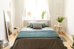 A big bed dressed in earth colors linen with cushions and a blanket standing in an eco friendly bedroom interior. Real photo. Concept stock photo