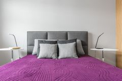 Big bed with grey pillows stock photo