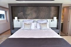 Big bed inside boat with many pillows and toilet and small door and window stock images
