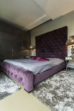 Big bed with violet pillows Stock Images