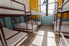 Big bedroom inside the hostel with clean beds of for lonely young tourists and students Stock Photography