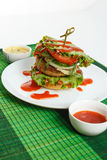 Big beef steak burger with vegetables and herbs on white plate on green bamboo placemat Stock Image