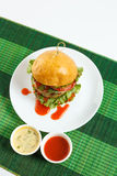Big beef steak burger with vegetables and herbs on white plate on green bamboo placemat Royalty Free Stock Image