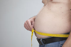 Big belly of a fat man. And measuring tape  on white Royalty Free Stock Image