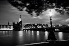 Big Ben, Λονδίνο το UK στο ηλιοβασίλεμα Αναδρομικό φως λαμπτήρων οδών στη γέφυρα του Γουέστμινστερ μαύρο λευκό Στοκ Εικόνες