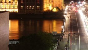 Big ben across westminster bridge at night tilt up right and zoom out stock footage