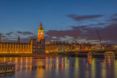 Big Ben clock, Westminster parliament and Westminster Bridge. Lighted Big Ben, Parliament and Westminster Bridge at night with some reflection on surface of Stock Photo