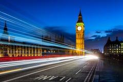 Big Ben e Londra alla notte con le luci del passaggio delle automobili Fotografia Stock