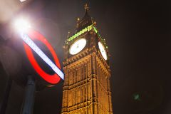 Big Ben and Houses of Parliament tube underground. Popular tourist Big Ben and Houses of Parliament and tube underground sign symbol in night lights illumination Stock Image