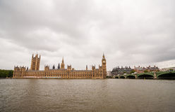 Big Ben husen av parlamentet och den Westminster bron på en molnig dag Royaltyfri Fotografi