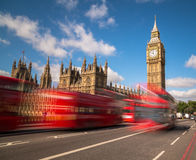 Big Ben and London Buses. Big Ben in Westminster with red London Buses going past during the day. There is space for text in the image Royalty Free Stock Photos