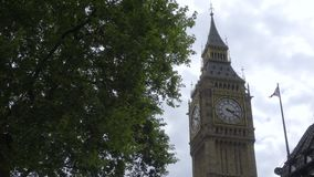 Big Ben near a British flag. Low angle view of Big Ben near a British flag stock video