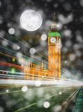 Big Ben at night with falling snow and full moon in London, UK. Elements of this image furnished by NASA Stock Photography