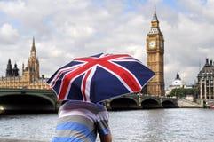 Big Ben och turist med det brittiska flaggaparaplyet i London Arkivbilder