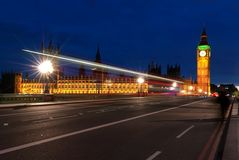 Big Ben, one of the most prominent symbols of both London and England, as shown at night along with the lights of the cars passing Royalty Free Stock Photo