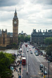 Big Ben Sunset. Big Ben in Westminster on a cloudy day. Cars and people cross the bridge royalty free stock photos